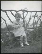 Magic Lantern slide -Young child (aged 4) - sitting on garden wall by trellis.