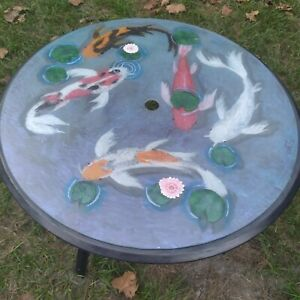 Outside patio table uniquely painted with coy fish swimming in a pond 3D look