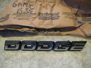 """MoPar Front Grille Nameplate """"DODGE"""" - NOS - '89-'92 Spirit - P/N 4388555"""