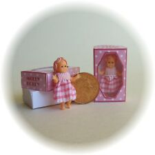 Molly Dolly, dolls house miniature toy doll in a box, wearing pink.