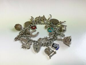 Vintage Silver Charm Bracelet with 27 charms and a silver padlock. 70.1 grams