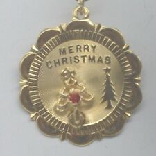 CW315   14 K GOLD  MERRY CHRISTMAS CHARM ON A ROUND DISK WITH  A RED STONE.