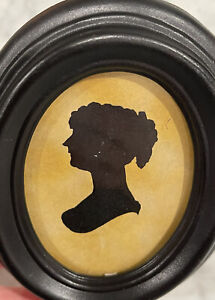 antique 19th century silhouette of a woman in a black oval frame.
