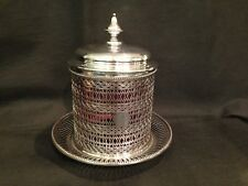 Antique silver plated pierced biscuit barrel with cranberry liner.