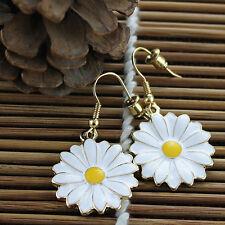 El oro y la flor blanca de la margarita del esmalte cuelgan los pendientes, 50s,