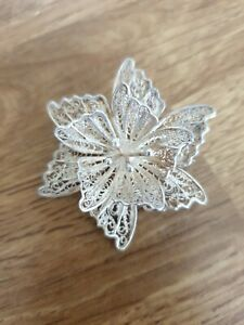 Silver filigree flower brooch. Two layers of petals and central stamens.
