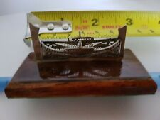 Small Silver Boat on wooden plinth.