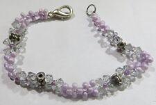 Bracelet artisanal avec nombreuses petites perles mauves et breloques plaquées a