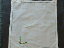 White cotton table napkin with hand embroidered Christmas holly on one corner.