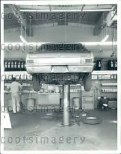 Shell Station Mechanics With Auto on Hydraulic Lift in Garage Press Photo
