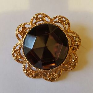 A beautiful gold tone brooch with a large amethyst coloured stone