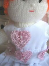 A HAND KNITTED DRESS UP DOLL WITH HAND MADE OUTFITS.
