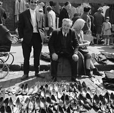 Photo. 1960s. Celtic Street Vendor Selling Used Shoes in Market