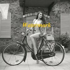 Woman On Bicycle In Front Of Brick Home-Photo