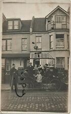 WW1 Belgian Refugees including a wounded soldier outside a large terraced house