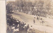 Postcard RPPC  Men running horses down dirt street crowds watching race 1910's?