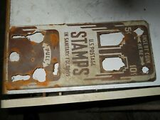 Very corroded front to old postage stamp machine
