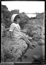 Petite fille assise rocher bord de mer - ancien négatif photo verre deb. XXe