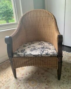 Wicker chair, wooden legs and arms, sold with seat pad.