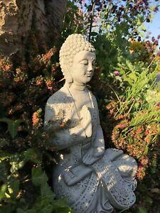 Buddha hand across chest resting stone garden ornament zen meditating