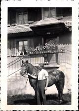 snapshot homme tenant un cheval longe devant maison bretelles mode vers 1930