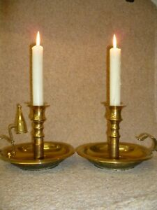 AN ANTIQUE PAIR OF 'WEE WILLIE WINKIE' BRASS CHAMBERSTICKS WITH CONICAL SNUFFER