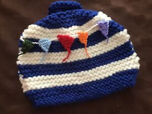 Hand knitted tea cosy.  blue and white striped decorated with bunting