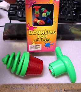 wind up spinning top, green plastic, crank top and hit button to release fun toy