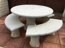 White stone circular garden table with 3 double benches.  Seats 6 people.