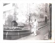 snapshot homme dans une rue avec fontaine habillé en blanc rural chapeau
