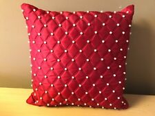 Red faux silk cushions with pearl detail