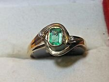 COLOMBIAN EMERALD SET IN A 14KT YELLOW GOLD RING WITH TWO DIAMOND