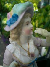 Sujet Porcelaine biscuit polychrome au naturel signé. Jeune femme à l'aumônière