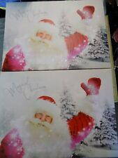 pair of magical Christmas light up Santa pictures
