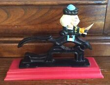 "Vintage Cast Iron Nutcracker On Wood Stand. 7.5"" X 5.5"". Red base"