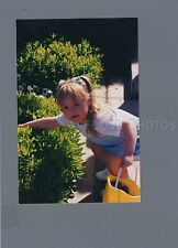 FOUND COLOR PHOTO C-177 SNAPSHOT GIRL SEARCHES FOR EASTER EGGS