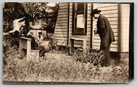 RPPC~Photo of Man Taking Picture of a Family Member on a Bench in Backyard~1909