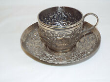 Antique Indian silver cup & saucer with repousse floral design.