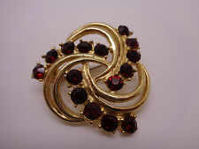 VINTAGE GOLD TONE BROOCH  METAL SWIRL WITH RUBY FACETED STONES