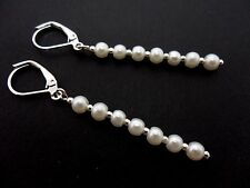 A PAIR OF DANGLY WHITE GLASS PEARL  SILVER PLATED LEVERBACK HOOK EARRINGS.