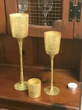 Three Candles Of Varying Heights In Gold Sparkled Candle Holders