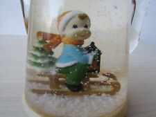 VINTAGE TEAPOT SNOW GLOBE OF CHILD ON SLED WITH XMAS TREE, MADE IN HONG KONG.
