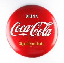 Placa em formato de botão da Coca-Cola