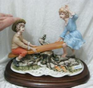 Capodimonte girl and boy on seesaw- damage to capodimonte plaque on front