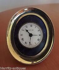 CARTIER  Pendulette reveil ovale en bronze doré. Cadran blanc, rond,