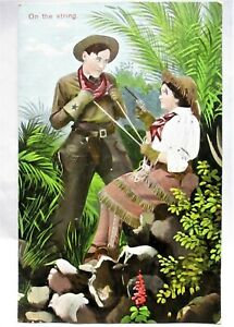 1908 POSTCARD COWBOY & COWGIRL, ON THE STRING,COWGIRL HOLDING HIM AT GUN POINT