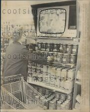 1970 Woman Shops Canned Goods While Watching TV Bonn Germany Press Photo