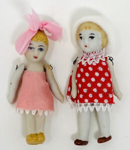 TWO TINY ANTIQUE ALL BISQUE DOLLS, WIRE JOINTS, MOLDLED HAIR, DRESSED
