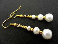 A PAIR OF DANGLY WHITE  GLASS PEARL  GOLD PLATED EARRINGS.