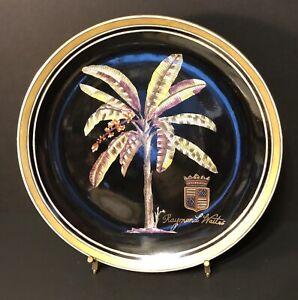 "Raymond Waites 10-1/4"" Decorative Wall Plate Image of Palm Tree w/Crest on Black"